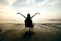 Relaxing business woman sitting on beach Stock Photography