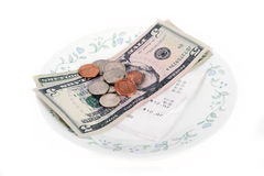 Restaurant bill with dollar bills (tips) on a plate Royalty Free Stock Photography
