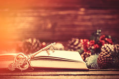 Retro book and key near Pine branches on a table. Royalty Free Stock Photo
