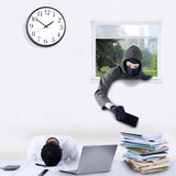 Robber stealing cellphone in office Royalty Free Stock Photo