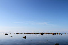 Rocks on calm waters Royalty Free Stock Images