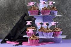Rosa färger och lilor för avläggande av examendag festar muffin och det stora locket Royaltyfria Bilder