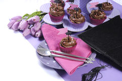 Rosa färger och lilor för avläggande av examendag festar tabellinställningen med muffin Arkivbild