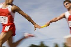 Runners Passing Baton In Relay Race Stock Image