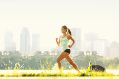 Running woman in city park - outdoor fitness Stock Photo