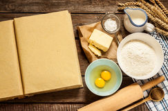 Rural kitchen baking cake ingredients and blank cook book Royalty Free Stock Photos