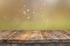 Rustic wood table in front of glitter green and gold bright bokeh lights Stock Photography