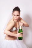 Sad bride with a bottle of champagne in hand Royalty Free Stock Image