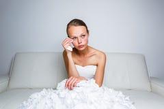 Sad bride crying sitting on a sofa Stock Photo