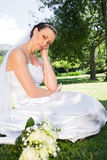 Sad bride with hand on chin in garden Stock Image