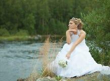 Sad bride sits on river bank Stock Image