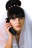 Sad bride speaks on the phone Stock Images
