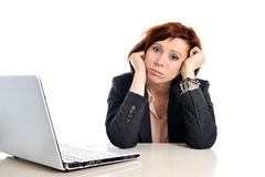 Sad business red haired woman in stress at work with computer Stock Image