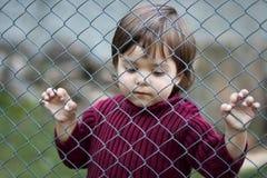 Sad child behind fence Stock Photography