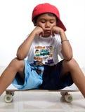 Sad little boy sitting on his skateboard Stock Photo