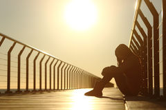 Sad teenager girl depressed sitting in a bridge at sunset Stock Photography
