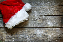 Santa Claus hat on vintage wooden boards christmas background Stock Images