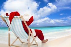 Santa Claus que se sienta en sillas de playa Concepto del día de fiesta de la Navidad Imagen de archivo