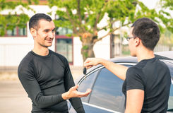 Satisfied buyer man receiving car keys after second hand sale Stock Photos