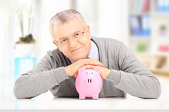 Satisfied gentleman posing over a piggy bank at his home Royalty Free Stock Photography