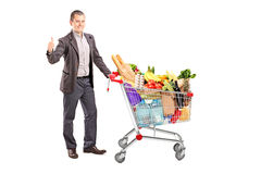 Satisfied man with a cart full of groceries Stock Photography