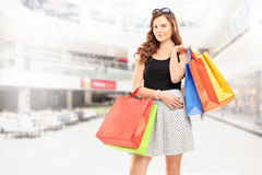 Satisfied young woman posing with shopping bags in a mall Stock Images