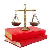 Scales of justice atop legal books Royalty Free Stock Image