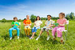 School mates hold exercise books sitting outside Stock Photos