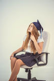 Schoolgirl with cap graduate sit on chair, thinking about future Royalty Free Stock Images