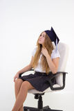 Schoolgirl with cap graduate sit on chair, thinking about future Stock Photo