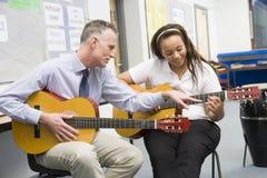 Schoolgirl and teacher playing guitar Royalty Free Stock Photos