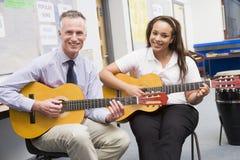 Schoolgirl and teacher playing guitar Stock Photo