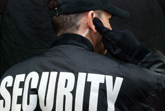Security Guard Listens To Earpiece, Back of Jacket Showing Royalty Free Stock Image