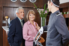 Senior couple at check-in at hotel Stock Images