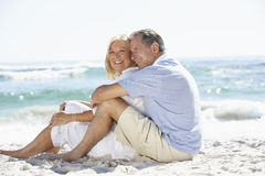 Senior Couple On Holiday Sitting On Sandy Beach Stock Photography