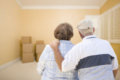 Senior Couple In Room Looking at Moving Boxes on Floor Stock Photo