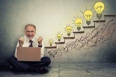 Senior executive man working on computer celebrates success Royalty Free Stock Image