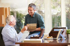 Senior Father Discussing Document With Adult Son Stock Photo