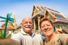 Senior happy couple taking a selfie at Grand Palace temples Royalty Free Stock Photo