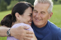 Senior Man Embracing Cheerful Woman Stock Photo