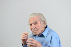Senior man taking the prescribed dose of medicine Royalty Free Stock Images