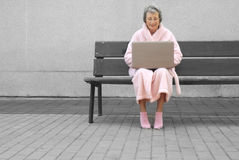 Senior woman in pink robe outdoors with laptop Royalty Free Stock Image
