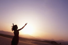 Serene young woman with arms outstretched doing yoga in the desert in China, Silhouette Stock Images