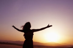 Serene young woman with arms outstretched doing yoga in the desert in China, Silhouette Stock Photography