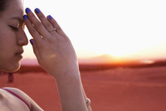 Serene young woman with eyes closed and hands together in prayer pose in the desert in China, side view Stock Photos