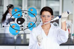 Serious chemist working with cell interface Stock Images