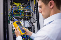 Serious technician using digital cable analyzer on server Royalty Free Stock Photography