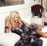 Sexy blond woman in lingerie and fur coat lying on bed with champagne Royalty Free Stock Photography