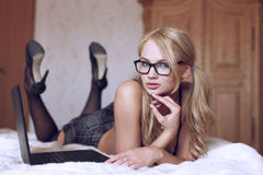 Sexy blonde student posing on bed with laptop Royalty Free Stock Images