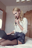 Sexy blonde woman kneeling with laptop Royalty Free Stock Photo
